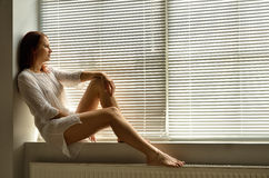 A woman on the windowsill at home Royalty Free Stock Photography