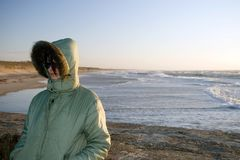 Woman at windy sea. The woman's wearing a warm winter coat, some useful copy space, sun from the back, clear blue sky Stock Photography