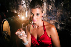 Woman in wine cellar with barrels tasting. Glass of vintage red Royalty Free Stock Photo