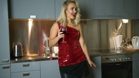 Woman with wine dancing in kitchen stock video footage