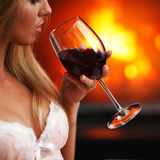 Woman with wine near fireplace Stock Photo