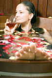 Woman with Wine in Tub - Vertical. Woman relaxes in a spa tub filled with flowers sips red wine. Vertically framed photograph stock images