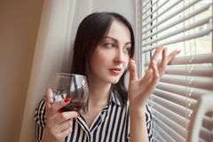 Woman with wineglass. Sad woman with wineglass looking at window Royalty Free Stock Photos