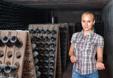 Woman winery employee standing in aging section with bottles Stock Images