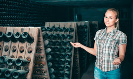 Woman winery employee standing in aging section with bottles Royalty Free Stock Photo