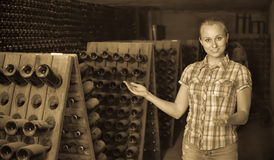 Woman winery employee standing in aging section with bottles Stock Image