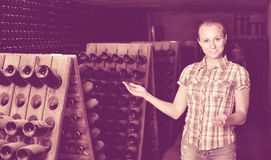 Woman winery employee standing in aging section with bottles. Young smiling  woman winery employee standing in aging section with bottles on winery manufactory Royalty Free Stock Photo