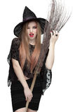 Woman winking eye in witch costume with a broom royalty free stock photo