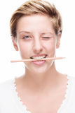 Woman winking with pencil in her mouth Royalty Free Stock Images
