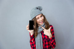 Woman winking and pointing finger on blank smartphone screen. Portrait of a cheerful woman winking and pointing finger on blank smartphone screen over gray Stock Image