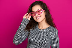 Woman winks, beautiful portrait, posing on pink background, long curly hair, sunglasses in heart shape, glamour concept Royalty Free Stock Images