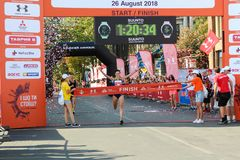 Woman winning race and coming first to finish. ODESSA, UKRAINE - CIRCA AUG 2018: Happy woman winning race and coming first to finish red ribbon royalty free stock photography