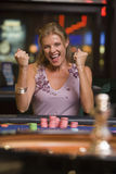 Woman winning at roulette table. In casino royalty free stock image