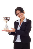 Woman winning a trophy. Portrait of an attractive young business woman winning a trophy against white background Royalty Free Stock Photos