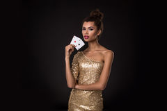 Woman winning - Young woman in a classy gold dress holding two aces, a poker of aces card combination. Stock Photography