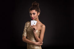Woman winning - Young woman in a classy gold dress holding two aces, a poker of aces card combination. Royalty Free Stock Image