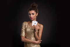 Woman winning - Young woman in a classy gold dress holding two aces, a poker of aces card combination. Royalty Free Stock Photography