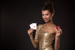 Woman winning - Young woman in a classy gold dress holding two aces and two red chips, a poker of aces card combination. Stock Photo