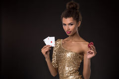 Woman winning - Young woman in a classy gold dress holding two aces and two red chips, a poker of aces card combination. Royalty Free Stock Image