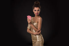 Woman winning - Young woman in a classy gold dress holding two cards, a poker of aces card combination. Emotions Royalty Free Stock Images