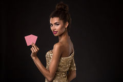 Woman winning - Young woman in a classy gold dress holding two cards, a poker of aces card combination. Royalty Free Stock Images