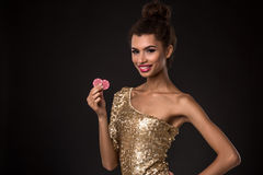 Woman winning - Young woman in a classy gold dress holding two red chips, a poker of aces card combination. Stock Photography