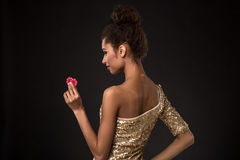 Woman winning - Young woman in a classy gold dress holding two red chips, a poker of aces card combination. Royalty Free Stock Photography