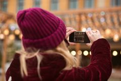 Woman in winter apparel taking photo on a smartphone with bokeh Stock Images