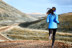Woman winter and autumn running in down jacket. Female running jogging on mountain trail in beautiful landscape Royalty Free Stock Photography