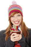 Woman with winter cap drinking something hot. Young woman with winter cap drinking something hot, isoalted on white Royalty Free Stock Images