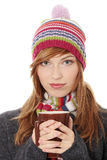 Woman with winter cap drinking something hot. Young woman with winter cap drinking something hot, isoalted on white Stock Photography