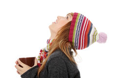 Woman with winter cap drinking something hot. Young woman with winter cap drinking something hot and looking up, isoalted on white Royalty Free Stock Image