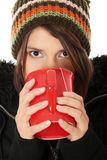 Woman with winter cap drinking something hot. Young woman with winter cap drinking something hot, isoalted on white Stock Image