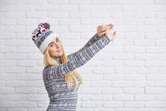 Woman in winter cap strecthing out Stock Images