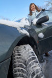 Woman winter car. Young woman and car in winter with tire in foreground royalty free stock photography