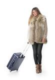 Woman in winter cl with a rolling suitcasothese. Royalty Free Stock Photography
