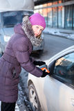 Woman at winter cleaning car windows Royalty Free Stock Photos
