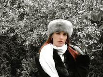 Woman in winter clothes. A young woman poses outdoors among some plants while dressed in a fur hat, scarf and coat. The background has been digitally altered to stock photography
