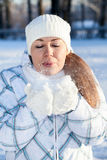 Woman in winter clothes blowing at snow in mittens Stock Image