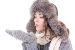 Woman in winter clothes blowing something from her palms isolate. D on white background Stock Photos