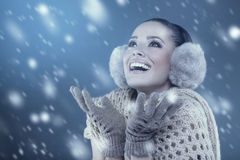 Woman in winter clothes catching snowflakes in the studio Stock Images