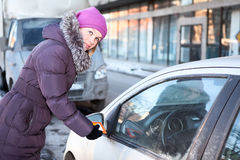 Woman in winter clothes cleaning car windows and mirrors before trip Stock Images