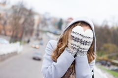 Woman in winter clothes covered face with mittens Royalty Free Stock Photos