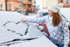 Woman in winter clothes drawing heart on car Royalty Free Stock Photography
