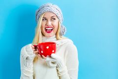 Woman in winter clothes drinking coffee Royalty Free Stock Image