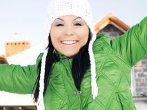 Woman in winter clothes enjoying in front of house Royalty Free Stock Image