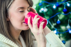 Woman in winter clothes enjoying a hot drink eyes closed. Portra Royalty Free Stock Image