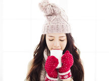 Woman in winter clothes having hot drink Royalty Free Stock Image