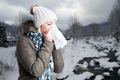 Woman in winter clothes holding a tissue to her nose. As cold and flu concept Royalty Free Stock Photo