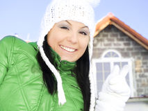 Woman in winter clothes pointing new house. Smiling woman in winter clothes pointing new house Royalty Free Stock Photos